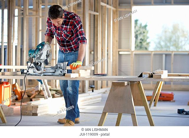 Carpenter using circular power saw to cut wood on indoor building construction site