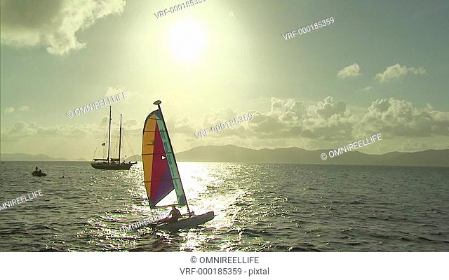 Male on small sailing Catamaran with sailboat behind and hills in distance with sun shining through clouds and reflecting off of sea