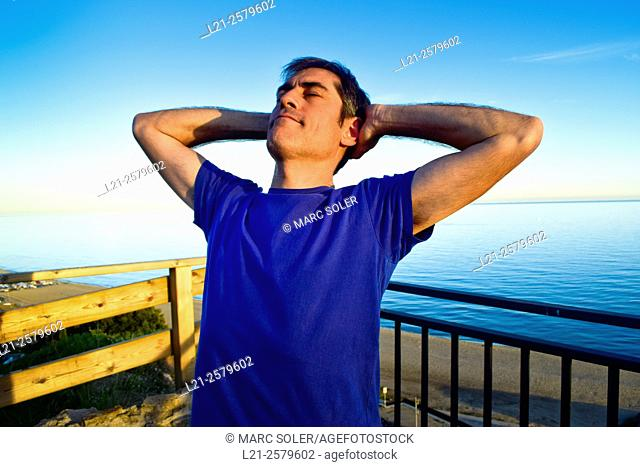 Man resting behind a railing near the sea, he is wearing a blue t-shirt