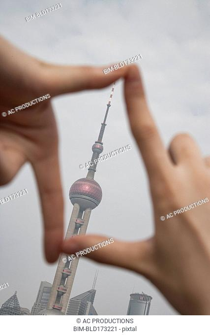 Chinese woman framing Shanghai tower, Shanghai, China