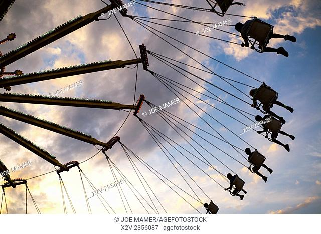 An amusement ride at a county fair sends riders soaring through the air at sunset