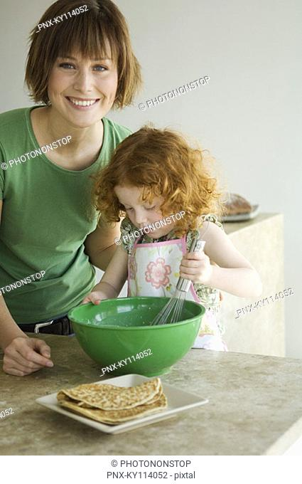 Woman and little girl cooking