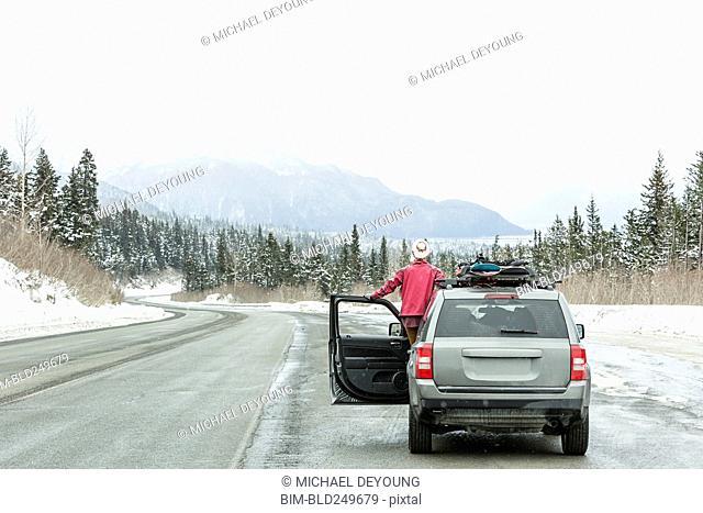 Caucasian woman standing in car in winter admiring scenic view