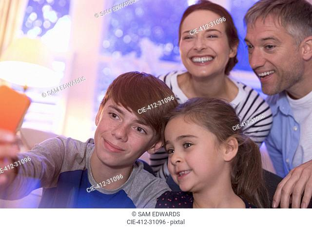 Smiling family taking selfie with camera phone