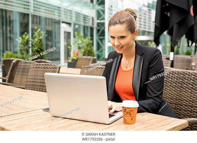 Young businesswoman with laptop and cell phone at a cafe