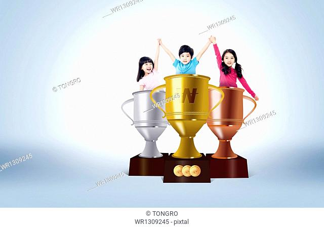 kids raising their hands while standing inside trophies