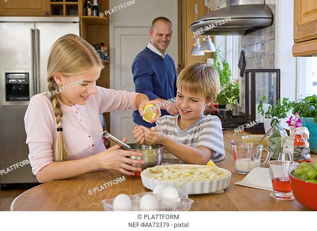 Sister and brother making a pie with their father, Sweden