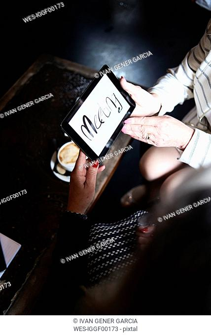 Two businesswomen with tablet having a meeting at a coffee shop