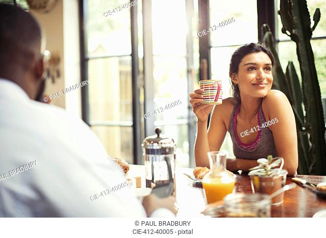 Smiling woman drinking coffee at breakfast table