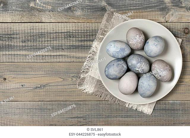 Natural dyed grey Easter eggs in plate with napkin on rustic grey wooden background. Top view point
