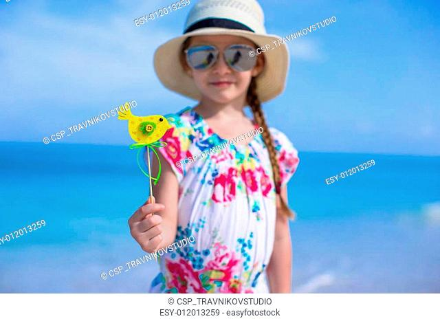 Happy little girl in hat on beach during summer vacation