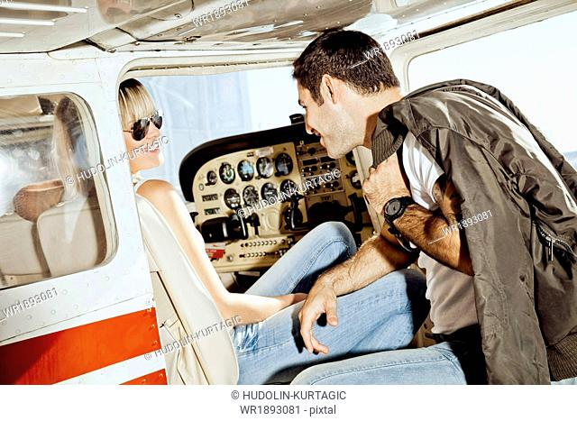 Young couple preparing for start in private airplane