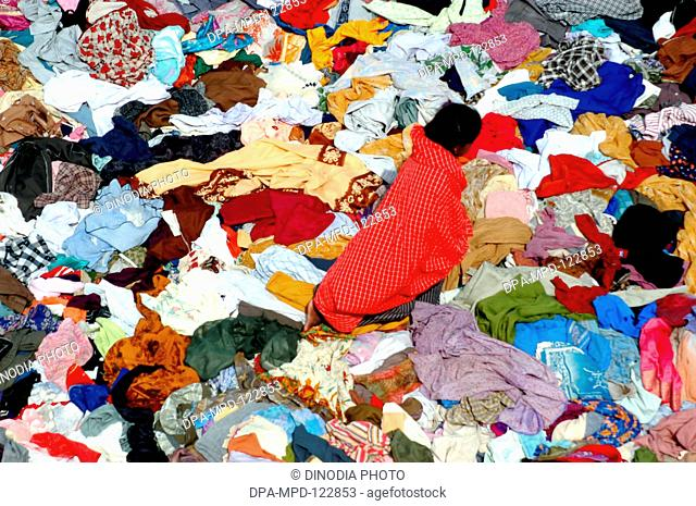 A girl selecting clothes from the stacks of clothes that arrived Nagapatinam following the Tsunami disaster as help from the people of the country as help for...