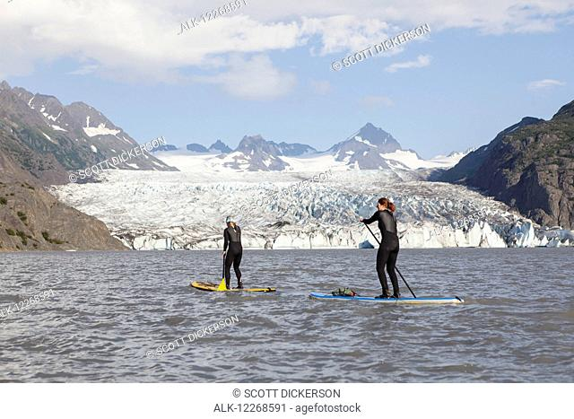 Two people stand up paddleboarding in front of Grewingk Glacier, Kachemak Bay State Park, Southcentral Alaska