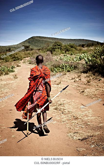 Maasai man walking on dirt road