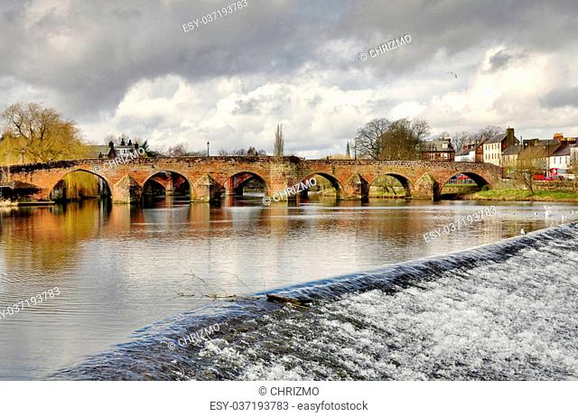 View of the historic 15th Century Devorgilla Bridge spanning the River Nith, with water cascading over the weir, on a winters day in Dumfries, Scotland
