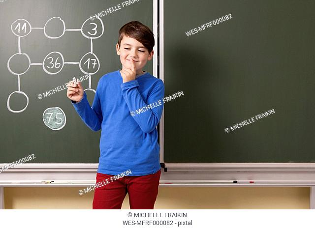 Schoolboy at blackboard with arithmetic problem