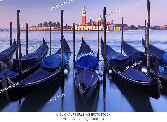 Europe, Italy, Veneto, Venice. The gondolas swaying rocked by the sea in the Grand Canal, in front of St. Giorgio Maggiore