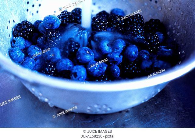 Blueberries and blackberries in a colander