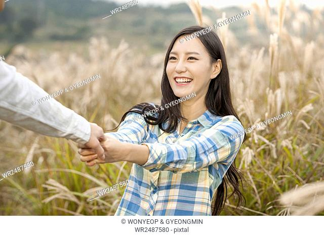 Portrait of young smiling woman holding hands with a man in silver grass field