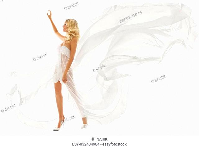 Beautiful woman in white dress with flying fabric walking over isolated background