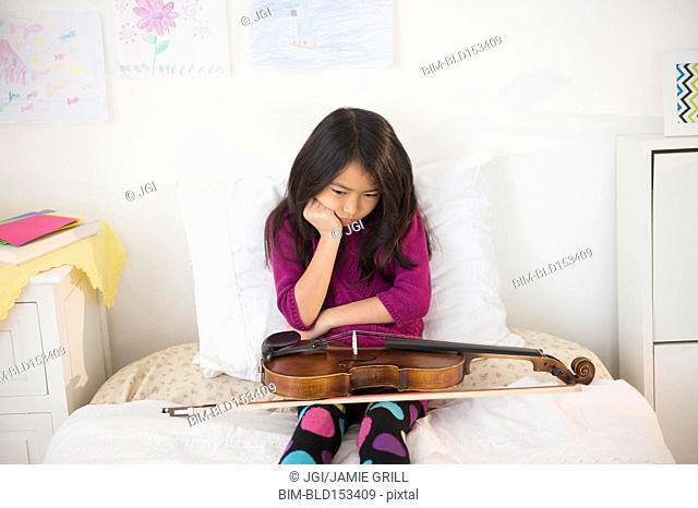 Pouting Vietnamese girl holding violin in bedroom