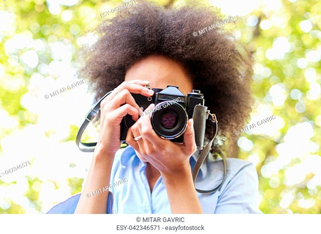 African american woman taking photo in nature with old retro camera , female photographer fun outdoor