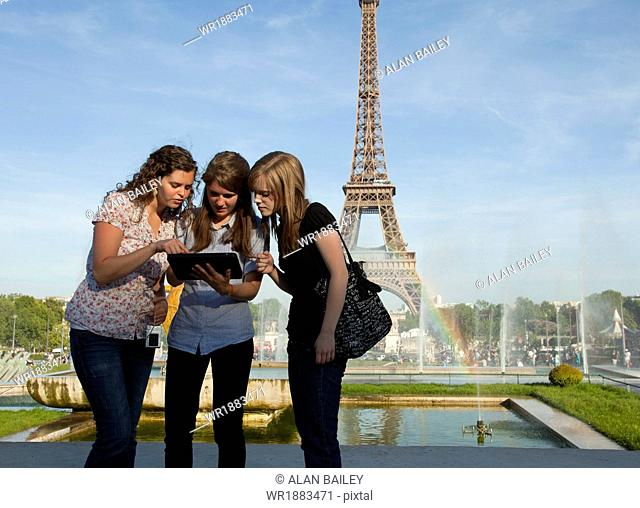 France, Paris, Three young women using tablet in front of Eiffel Tower