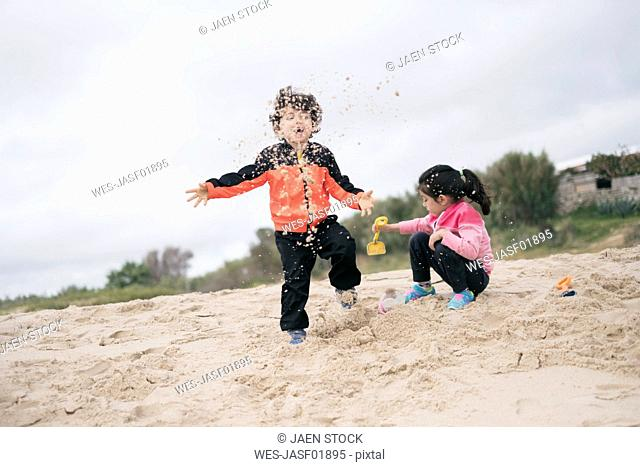 Brother and sister playing on the beach with sand