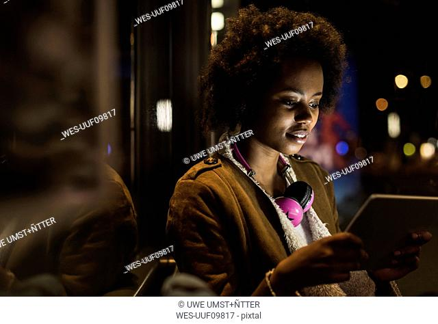 Young woman with headphones usinf tablet while waiting at the tram stop