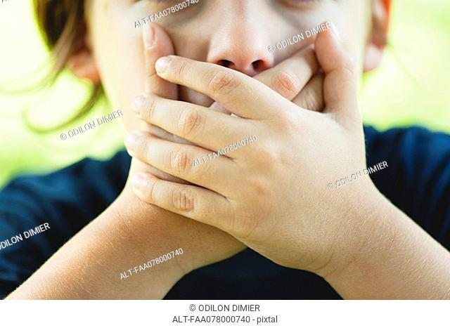 Boy covering mouth with hands, cropped