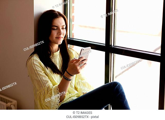 Teenage girl reading text message on cellphone by glass window