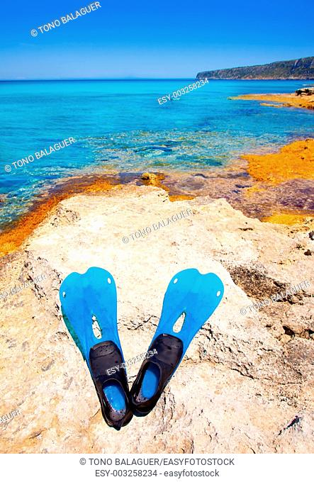 Balearic Formentera island with scuba diving blue fins on a rock