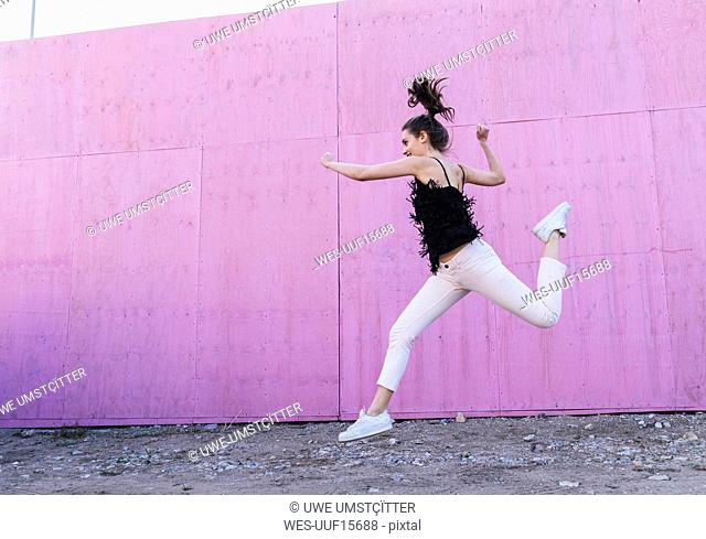 Exuberant young woman jumping in front of pink wall