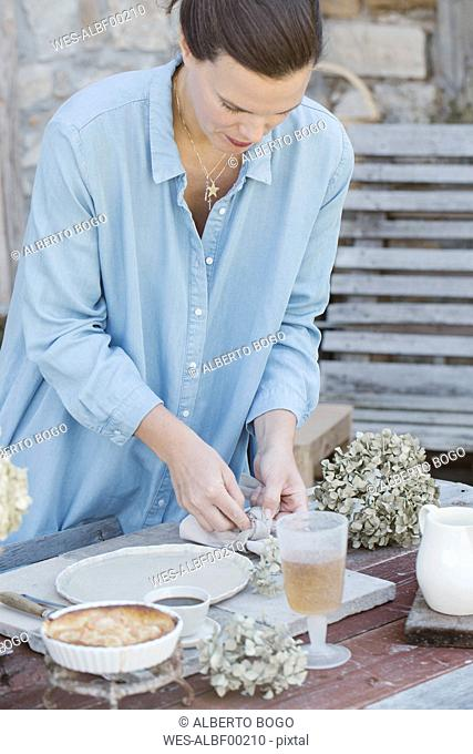 Italy, woman laying breakfast table on terrace