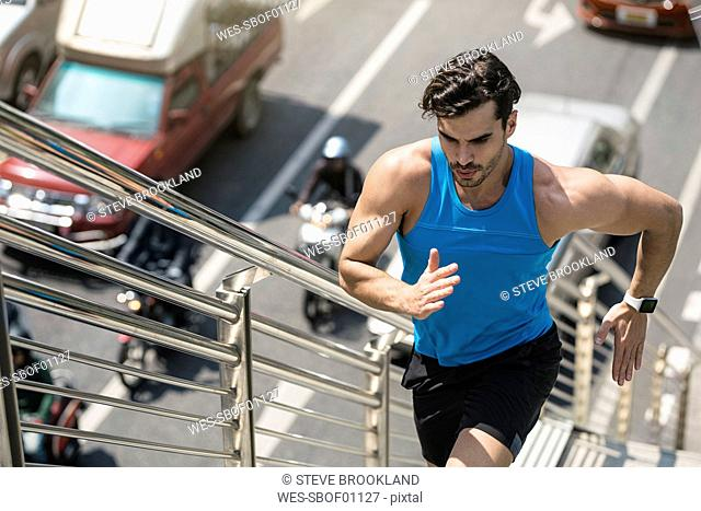 Man in blue fitness shirt running upstairs in city