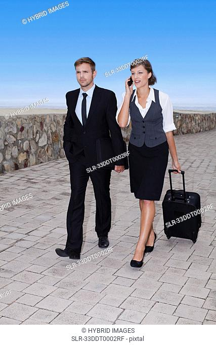 Business people rolling luggage