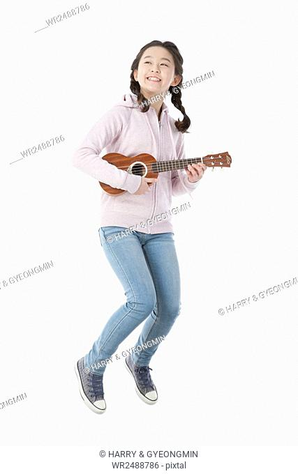 Smiling school girl with ukulele jumping