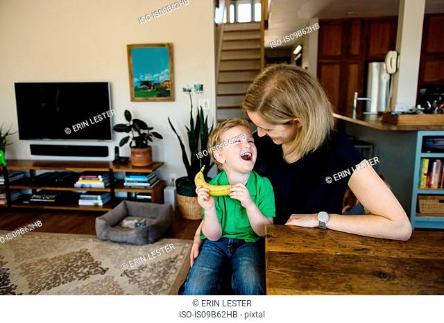 Boy sitting on mother's lap laughing