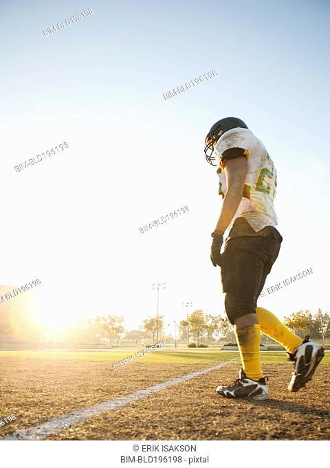 Hispanic football player walking on football field