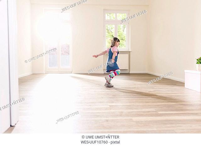 Happy girl running in empty apartment