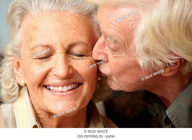 Senior man kissing senior woman on cheek