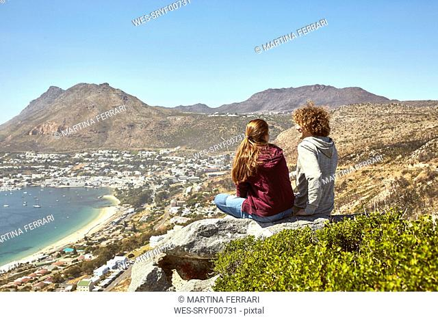 South Africa, Cape Town, young couple sitting at the coast looking at view