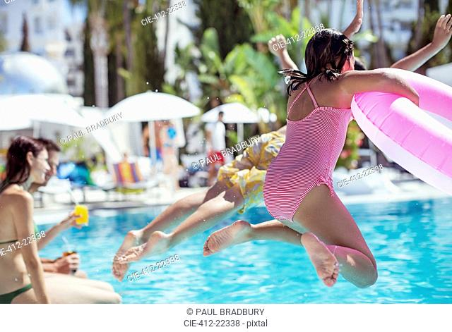 Children jumping into resort swimming pool