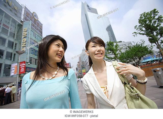 Young women smiling, low angle view