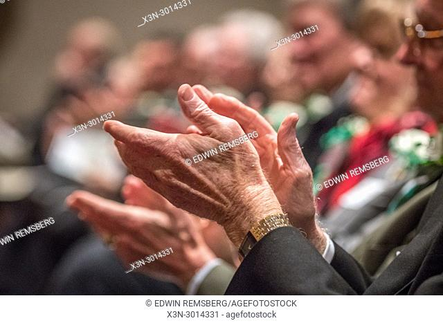 Elderly man clapping his hands in applause in auditorium, Chevy Chase, Maryland, USA