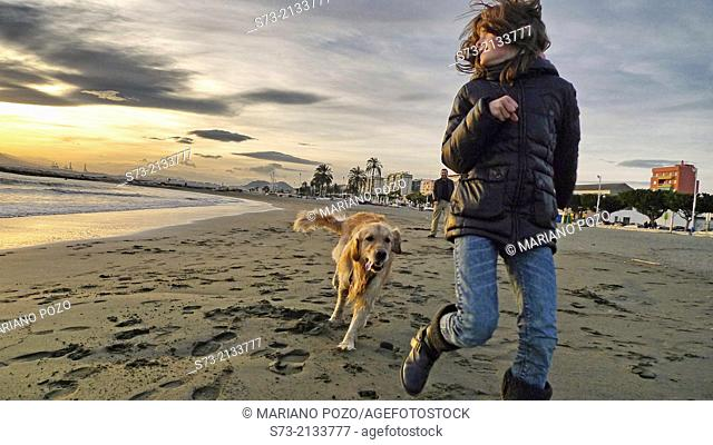 Girl playing with dog in the beach, Pedregalejo beach, Málaga, Andalucía, Spain