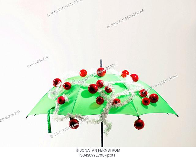 Green umbrella with Christmas decorations against white background