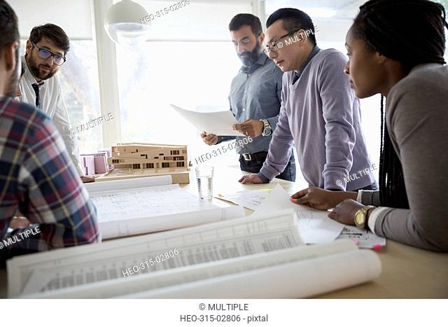 Architects reviewing blueprints and paperwork in office
