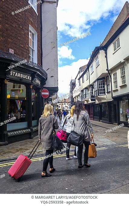 Tourists with suitcases walking in the streets of the Old Town in York, North Lanarkshire, England, United Kingdom, Europe